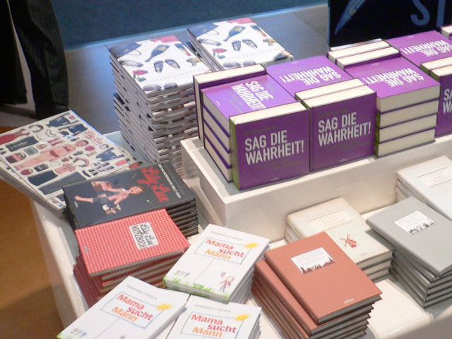 Foto vom Tisch mit dem Buch Die wunderbare Welt der Lily Lux, Lily Lux Notizbuch, und Lily Lux Kühlschrankmagneten am Stand von Hoffmann und Campe auf der Frankfurter Buchmesse